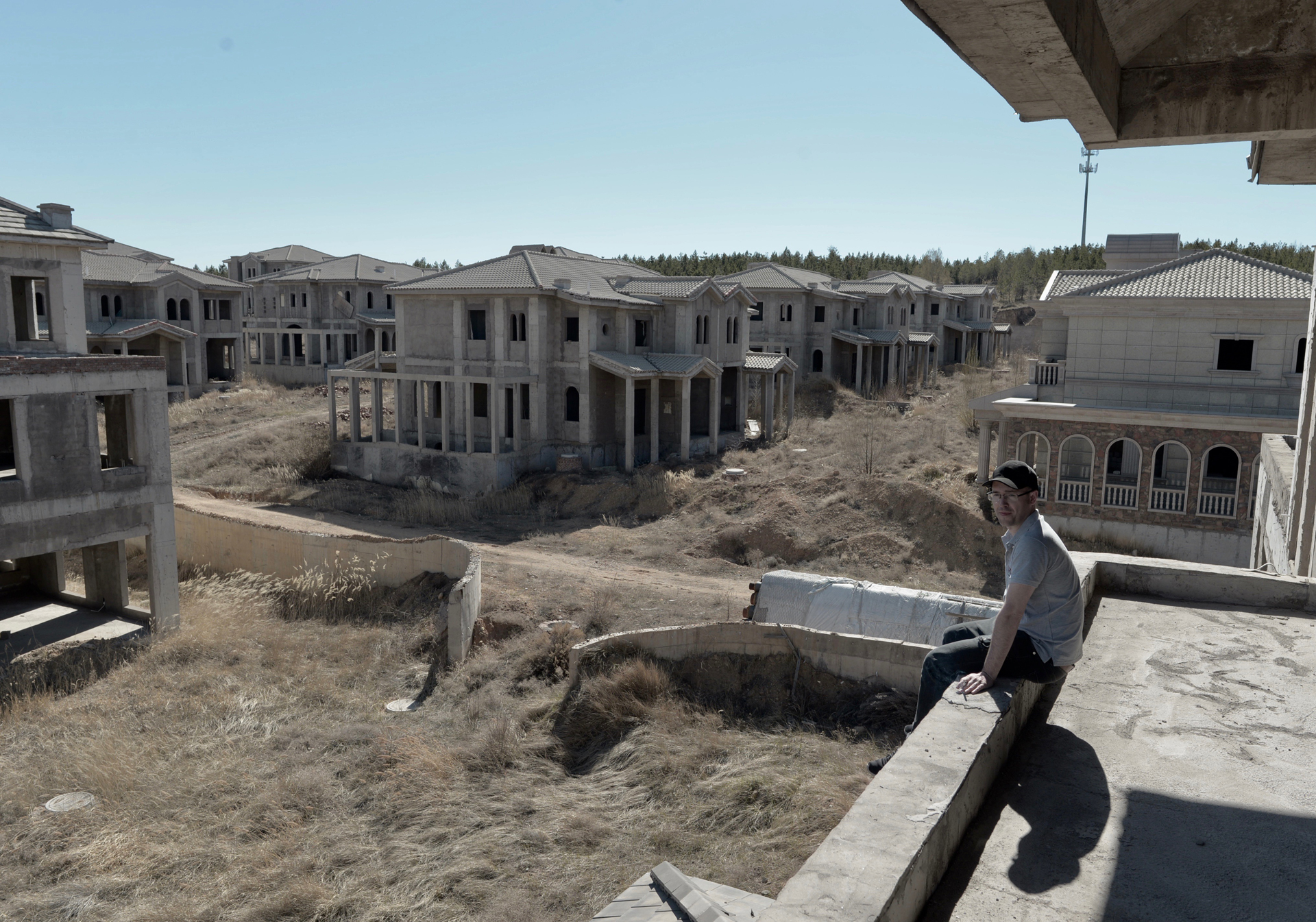 A man looks out over the empty buildings of Ordos Kangbashi.