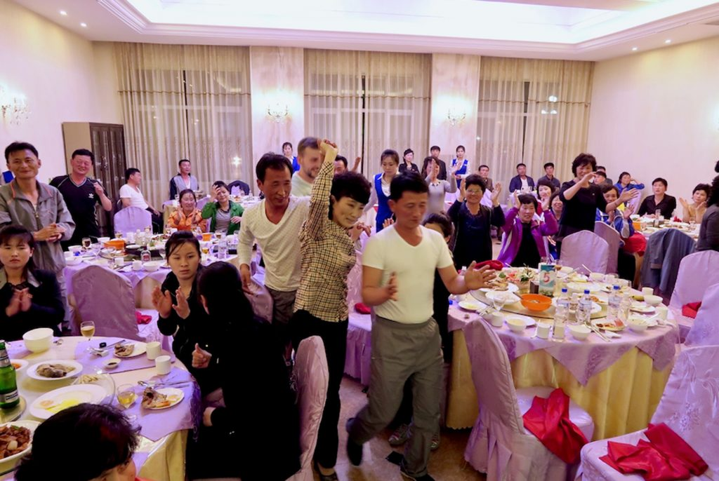 A group of foreigners and Koreans dance in a restaurant in Sinuiju.