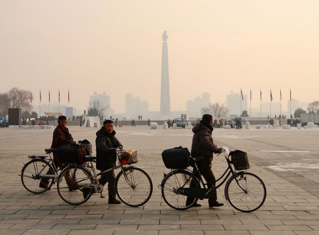Cycling people walking next to Kim Il Sung Square during winter