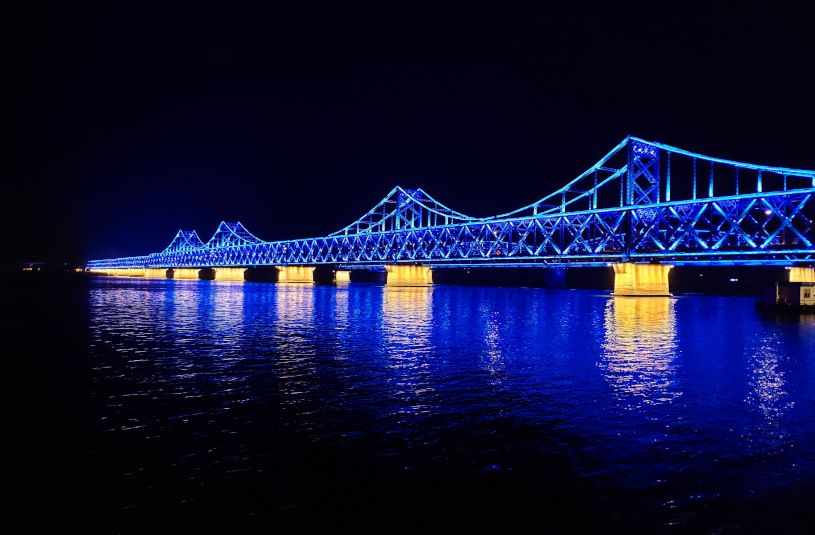 A picture of the rail bridge conencting Dandong and Sinuiju at night. The blue and yellow lights on the bridge reflect off the Yalu River.