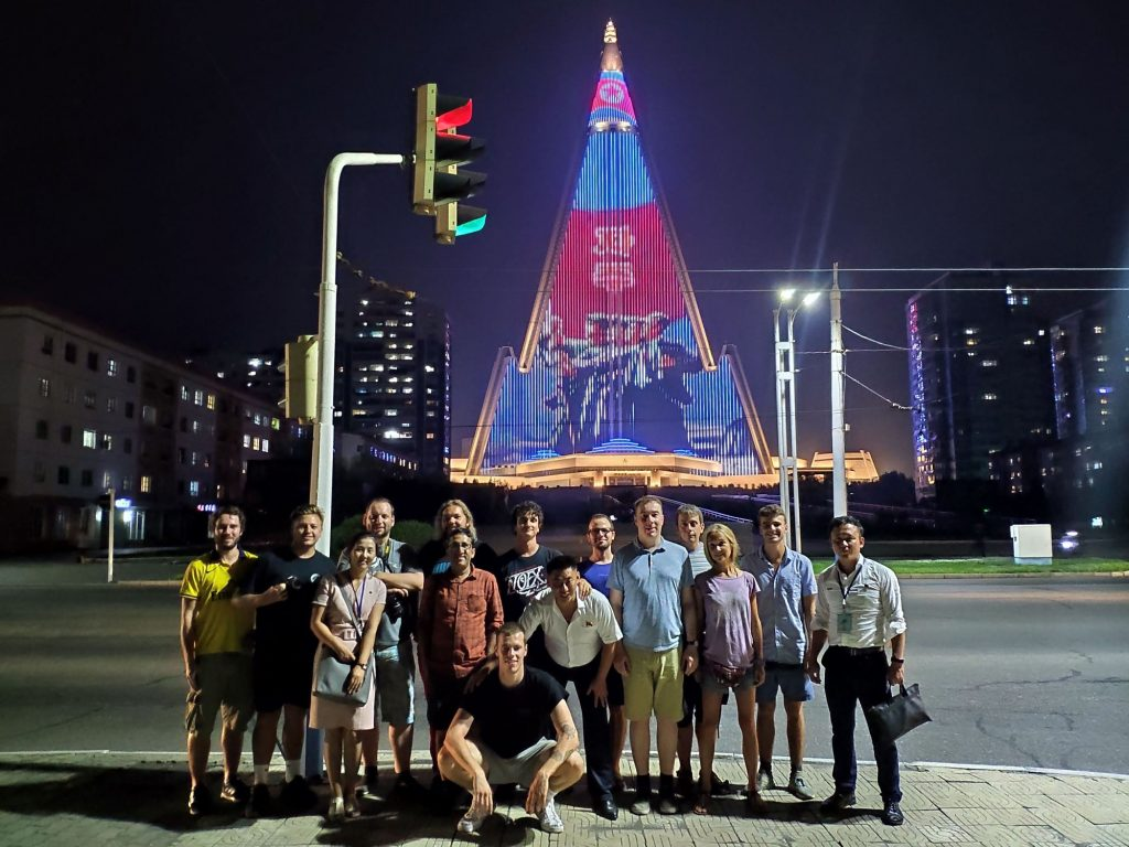 The illuminated pyramid hotel of Pyongyang stands behind our group. The illuminated Ryugyong hotel