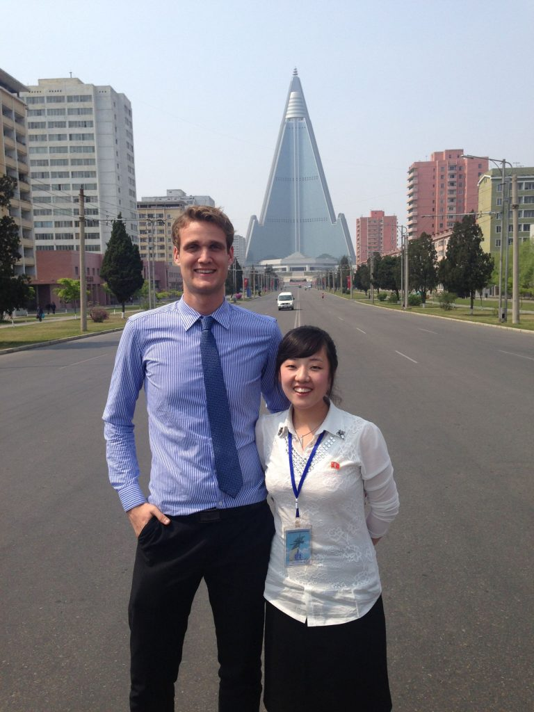 YPT guide rowan is with a local guide in front of the Ryugyong Hotel