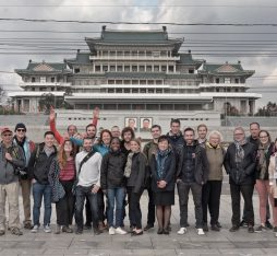 A group of smiling tourists pose in front of Grand People's Study House in Pyongyang.