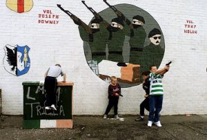 Northern Irish children play with guns in front of an AK-47 mural in Belfast.