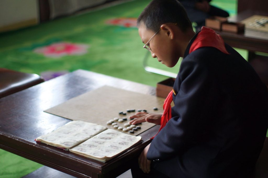 A kid playing Korean chess at the Children's palace