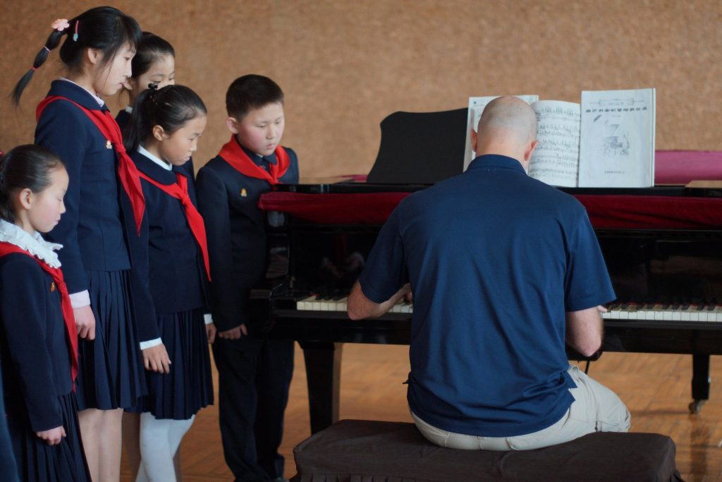 A guest playing piano to North Korean Children at the Mangyongdae School Children's Palace