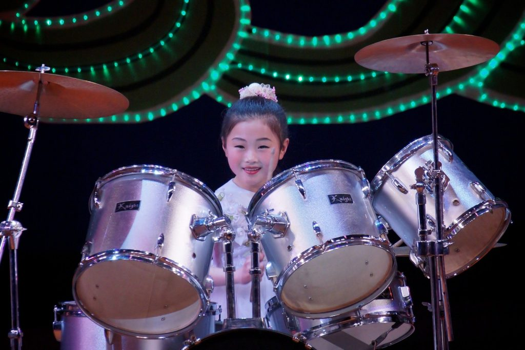 A north korean drummer girl is throwing a performance at the Mangyongdae Children's palace