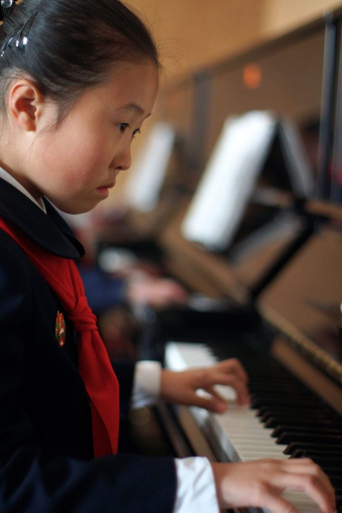 A girl playing piano during her afterschool classes in Mangyongdae