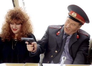 A police officer brandishing a firearm whilst a woman looks on in Transnistria.