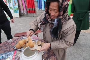 """""""Grandmother Makgeolli"""" prepares bowls of the fermented rice drink for tourists."""