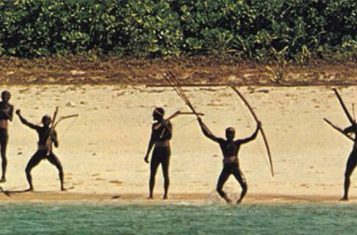 A shot of the North Sentinel Island tribe waving their bows from the beach
