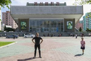 North Korea documentary: Justin Martell stands in front of Kaeson Cinema in North Korea.