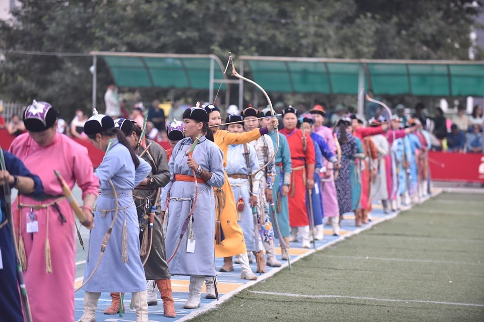 A line of women dressed in colourful traditional deels prepare to demonstrate their Mongolian archery skills at the Naadam archery competition.