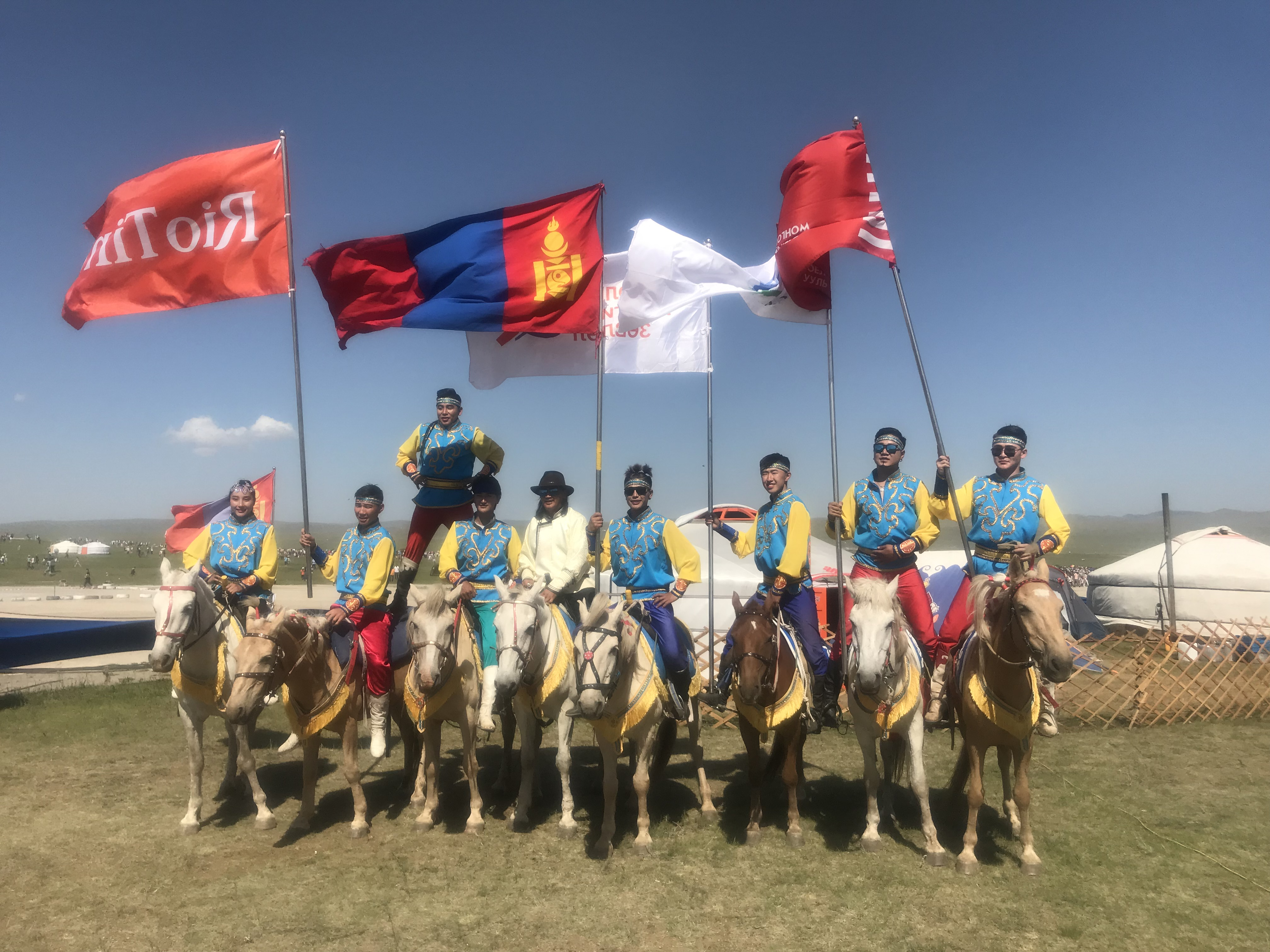 A group of Mongolian riders pose after a Mongol horse race.