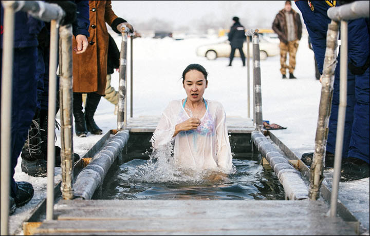 Festivals in Transnistria: a young woman wearing a transparent white robe and bikini plunges into freezing waters during the Orthodox Epiphany festival in Transnistria.