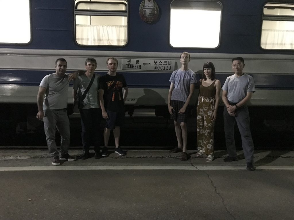 Six tourists stand in front of the Moscow-Pyongyang train carriage.