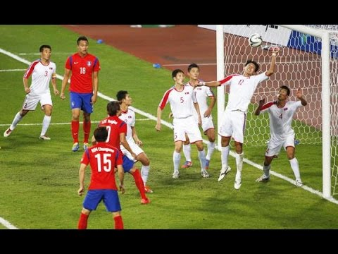 North Korea South Korea football: South Korea head the ball past the North Korean defenders in the 2014 Asian Cup.