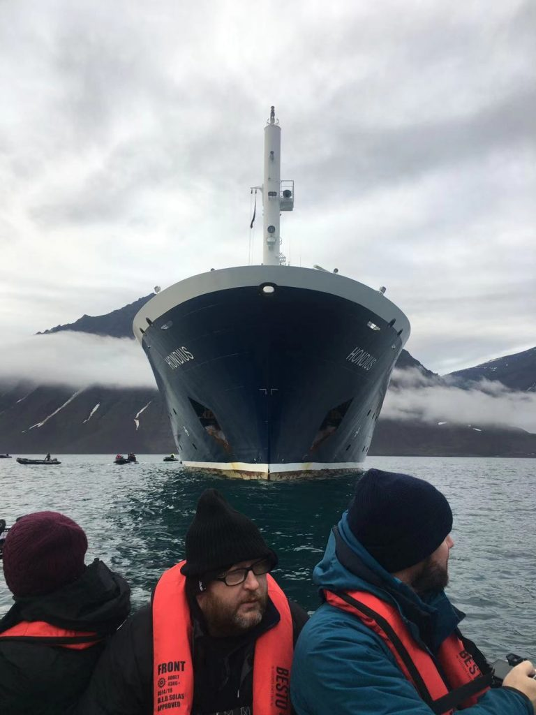 The cruise ship MV Hondius sits in the water behind a group of tourist making landfall in a zodiac (a sturdy rubber dinghy).