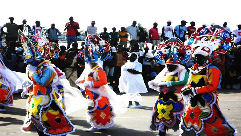 Onlookers watch as Angolan Carnival participants dance by.