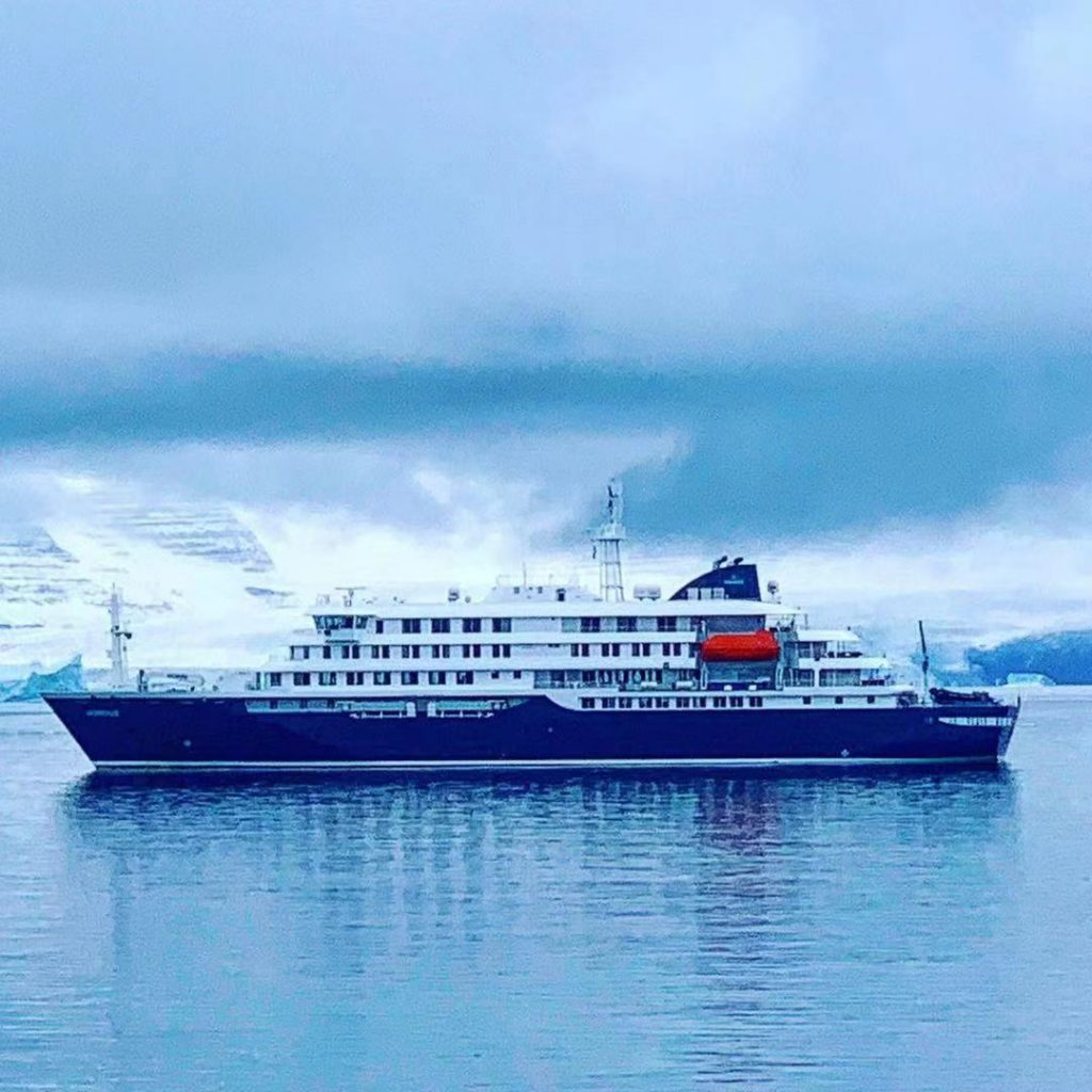The ship that took us on our Greenland cruise sits in the still ocean under a cloudy sky.