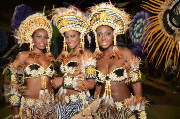 Three women in flamboyant costumes pose at the Angola Carnival.