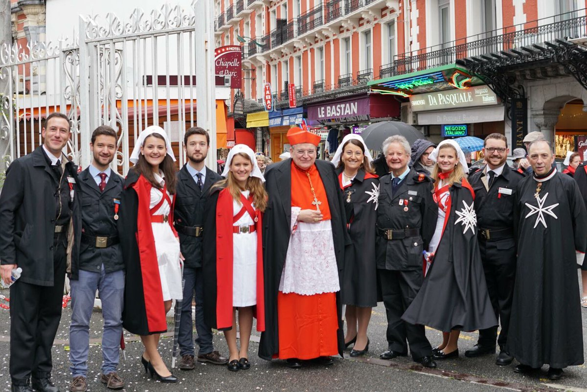 Dames and Knights of the Sovereign Military Order of Malta pose for a photo in the street.