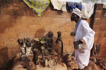 A voodoo priest making offerings to voodoo idols in Abomey