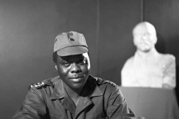 The young Mathieu Kerekou, standing in front of a bust of Lenin