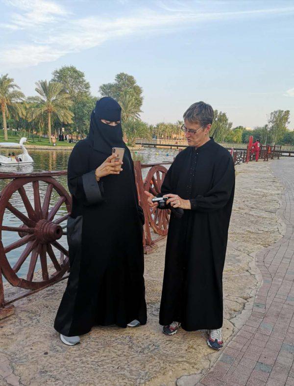 A female traveller in Saudi Arabia picks up a conversation with a local women in a park, in Riyadh