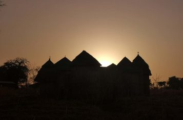 The silhouette of a tata house against the sunset