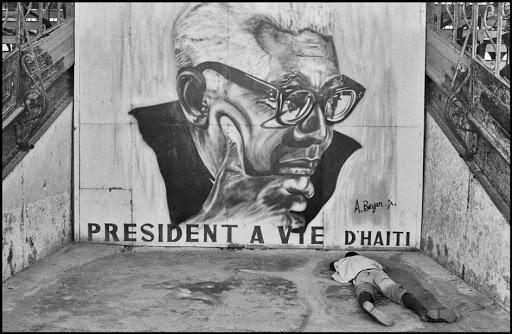 Homeless man under Papa Doc mural