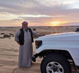 A bedouin guide by his car in the White Desert of Egypt