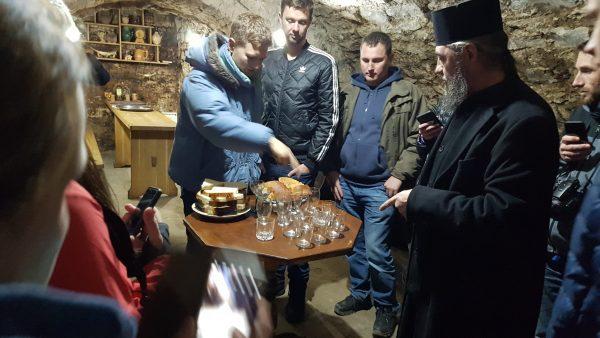 An orthodox priest arranges wine tasting